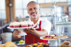 Happy barista smiling at camera and holding a plate of cupcakes Royalty Free Stock Image
