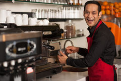 Happy barista staff preparing the order. Cheerful male staff preparing customers order Stock Image
