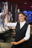 Happy barmaid pulling a pint of beer Royalty Free Stock Photos