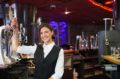 Happy barmaid pulling a pint of beer Royalty Free Stock Images
