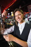 Happy barmaid pulling a pint of beer Stock Photo
