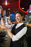Happy barmaid pulling a pint of beer Stock Photos