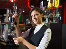Happy barmaid pulling a pint of beer Stock Photography
