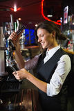 Happy barmaid pulling a pint of beer Stock Images