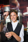Happy barmaid pulling a pint of beer Stock Image