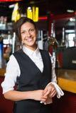 Happy barmaid smiling at camera Royalty Free Stock Photography