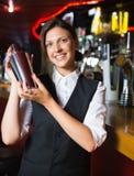 Happy barmaid smiling at camera making cocktail Royalty Free Stock Image