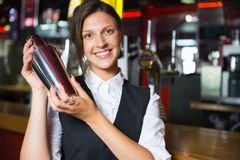 Happy barmaid smiling at camera making cocktail Royalty Free Stock Images