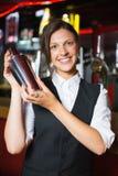 Happy barmaid smiling at camera making cocktail Royalty Free Stock Photo