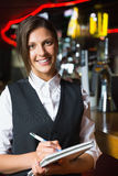 Happy barmaid smiling at camera taking notes Stock Images