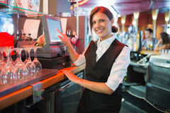 Happy barmaid using touchscreen till Royalty Free Stock Photo