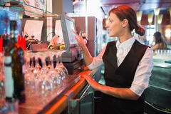 Happy barmaid using touchscreen till Stock Photography