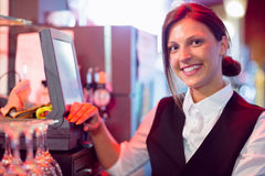 Happy barmaid using touchscreen till Royalty Free Stock Images