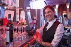 Happy barmaid using touchscreen till Stock Photo