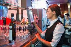 Happy barmaid using touchscreen till Stock Photos
