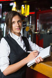 Happy barmaid writing in notepad Royalty Free Stock Photography