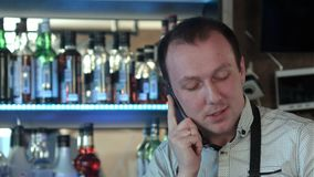 Happy barman in apron calling on smartphone at bar. Close up. Professional shot in 4K resolution. 086. You can use it e.g. in your commercial video, business stock video footage