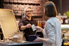 Happy barman and woman paying money at cafe Royalty Free Stock Image