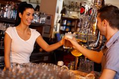 Happy bartender handing glass of bear to customer Royalty Free Stock Images