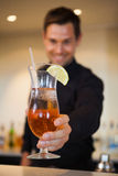 Happy bartender offering cocktail to camera Royalty Free Stock Images