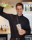 Happy bartender preparing a cocktail Royalty Free Stock Images