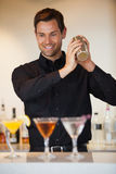 Happy bartender shaking cocktails Stock Photography