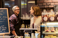 Happy bartenders at cafe or coffee shop counter Stock Images