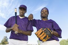 Happy Baseball Players Standing Against Sky Stock Images