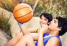 Happy basketball players. Cute basketball players sitting and resting in timeout, two teenage boys enjoying outdoor game, happy healthy active lifestyle royalty free stock photo
