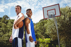 Happy basketball players standing back to back Royalty Free Stock Photo