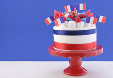 Happy Bastille Day celebration cake. With flags, marshmallow and candy decorations on a red cake stand on a white table against a blue  background Stock Images