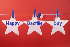 Happy Bastille Day greeting. Celebrate France's national holiday, on 14th of July, with Happy Bastille Day greeting written across white stars with a French flag Royalty Free Stock Images