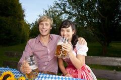 Happy bavarian couple in beer garden stock photography