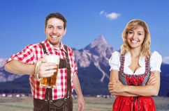 Happy bavarian man with beer mug and blonde woman with dirndl ce. Happy bavarian men with beer mug and blonde women with dirndl celebrating the oktoberfest with royalty free stock photo
