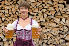 Happy Bavarian woman holding two tankards of beer Stock Photos