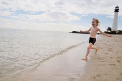Happy on the beach. Happy boy on the beach running into the water Royalty Free Stock Photo