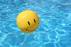 Happy beach ball. Yellow smiley face ball floating in a swimming pool Royalty Free Stock Photo