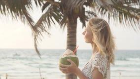 Happy beach bikini woman relaxing drinking fresh coconut water lying down sunbathing on fun Caribbean vacation stock footage
