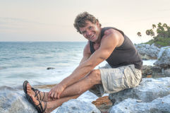 Happy beach bum. Handsome muscular Caucasian man with happy smile as he sits on rocky Caribbean seashore stretching his legs wearing sandals, shorts and tank top Royalty Free Stock Photos