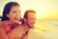 Happy beach fun multicultural couple - summer love. In sunset. Young adults piggybacking playful and laughing on hawaiian beach, Asian women and Caucasian man Stock Images