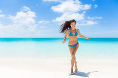 Happy beach summer fun bikini woman running of joy. Happy beach summer fun Asian bikini woman running of joy on amazing white sand enjoying holidays on Caribbean royalty free stock images