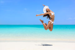 Happy beach woman jumping of weight loss success. Happy bikini woman jumping of joy on beach. Excited holiday girl doing a jump of freedom and happiness in a Stock Images