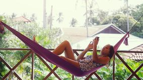 Happy beach woman reading sms texting on smartphone lying on hammock relaxing on tropical vacation. Slow motion. Happy beach woman reading sms texting on stock footage