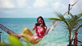 Happy beach woman wearing sunglasses taking selfie with mobile phone and sea view lying on hammock relaxing on tropical stock footage
