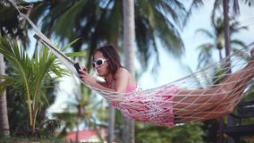 Happy beach woman reading sms texting on smartphone lying on hammock relaxing on tropical vacation. 1920x1080 stock video footage