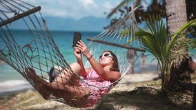Young cute girl wearing sunglasses lying down in outdoor swing bed enjoying sun sunbathing taking selfie with mobile. Happy beach woman reading sms texting on stock video