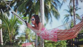 Happy beach woman uses smartphone lying on hammock relaxing on tropical vacation. 1920x1080, hd stock video footage