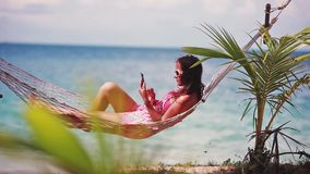 Happy beach woman wearing sunglasses reading sms texting on smartphone lying on hammock relaxing on tropical vacation stock video