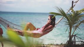 Happy beach woman wearing sunglasses talking mobile phone lying on hammock relaxing on tropical vacation with amazing. Sea view. 1920x1080, hd stock video footage