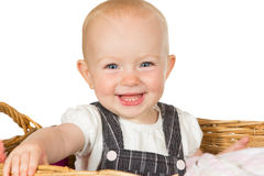 Happy beaming baby. Adorable happy beaming baby with a wide toothy smile sitting in a wicker basket isolated on white Stock Photography